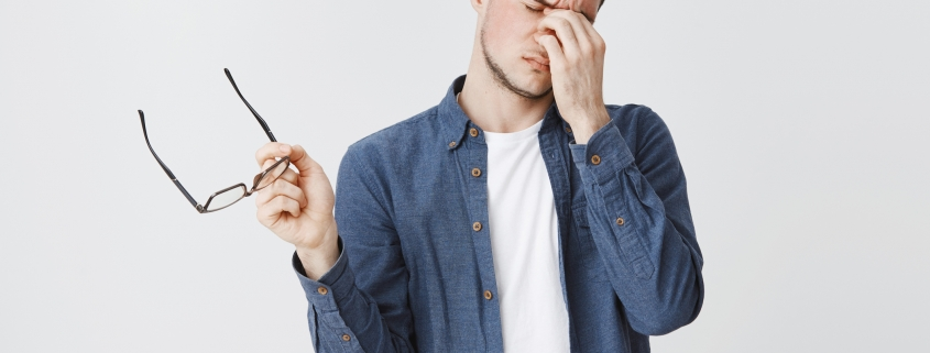 Guy rubbing eyes as feeling tired after wearing glasses while working over freelance project on computer standing with eyewear in hand and closed eyes being drained and exhausted, being hardworking