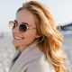Close-up portrait of positive girl with wavy blonde hair dressed in beige cashmere sweater and sunglasses on beach.